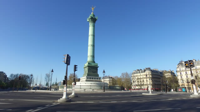 bastille square with no traffic, with a few people walking on april 05, 2020 in paris, france. the country is issuing fines for people caught... - バスティーユ点の映像素材/bロール