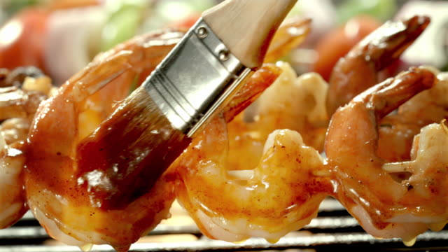 ecu basting brush adds second layer of barbecue sauce over shrimp on skewers on open flame grill - bbq brush stock videos and b-roll footage