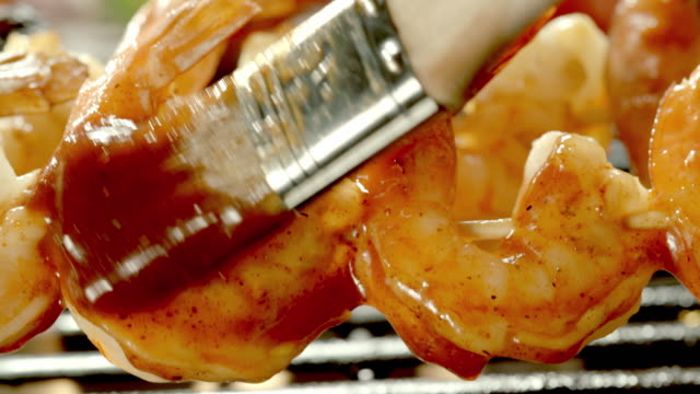 a basting brush swipes barbecue sauce on shrimp as it cooks over an open flame. - bbq brush stock videos and b-roll footage