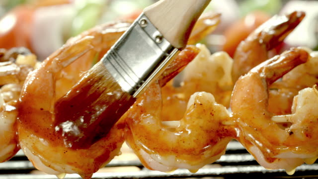 ecu basting brush swipes barbecue sauce over three shrimp on skewers on open flame grill - bbq brush stock videos and b-roll footage