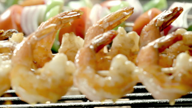 A basting brush swipes olive oil on shrimp as it cooks over an open flame.