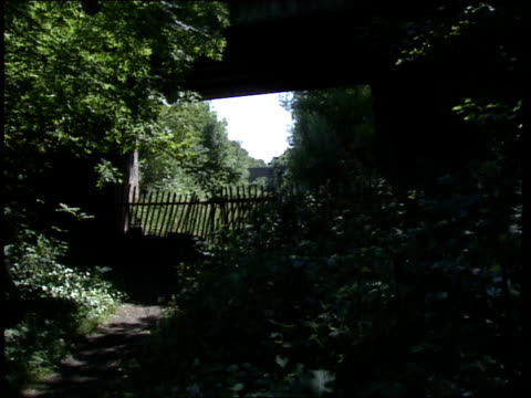 09 cr568 bat england west sussex 0230 gv disused station house sign 'danger keep out' overgrown path railway bridges people walk away down overgrown... - keep out sign stock videos & royalty-free footage
