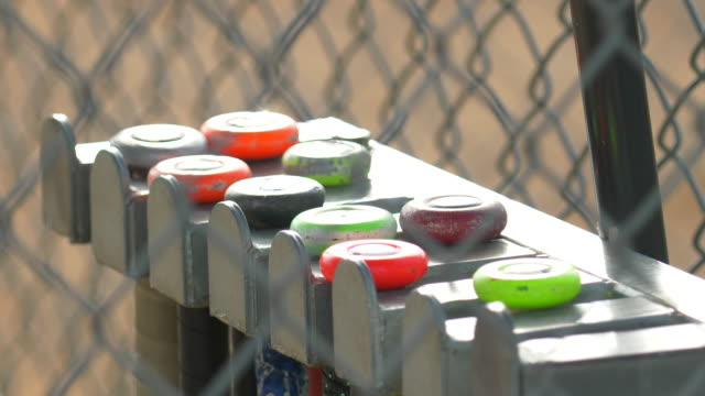 a bat rack full of bats in the dugout at a little league baseball game. - baseball bat stock videos & royalty-free footage
