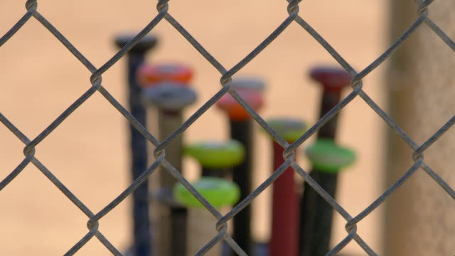 a bat rack full of bats in the dugout at a little league baseball game. - batting sports activity stock videos and b-roll footage