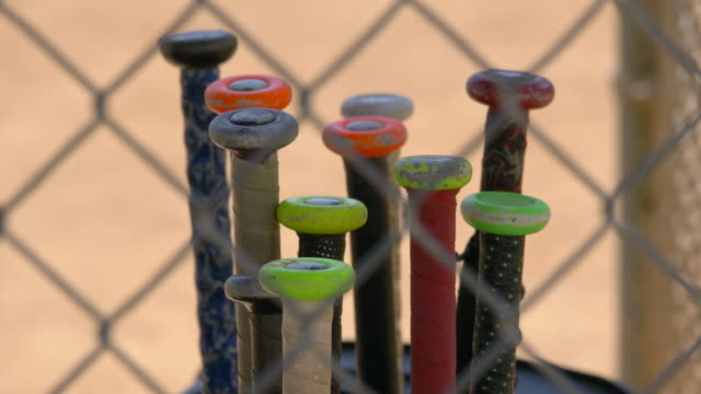 a bat rack full of bats in the dugout at a little league baseball game. - little league stock videos and b-roll footage