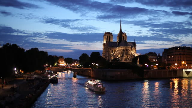 WS HA Bateau Mouche on Seine river at dusk, Notre-Dame cathedral in distance / Paris, France