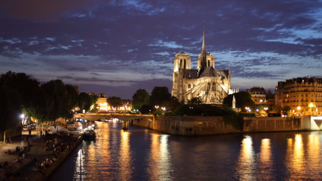 T/L WS Bateau Mouche on Seine river with Notre Dame cathedral in distance, dusk to night / Paris, France