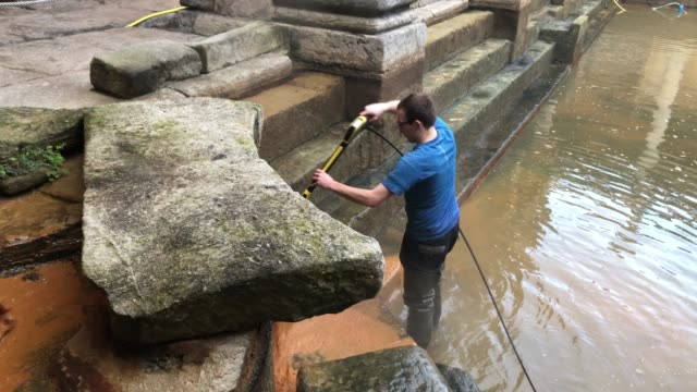 bath and north east somerset council contractors brush algae and sludge from the original roman lead lined floor of the great bath as it is drained... - guter zustand stock-videos und b-roll-filmmaterial