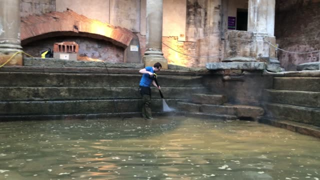 bath and north east somerset council employees brush algae and sludge from the original roman lead lined floor of the great bath as it is drained of... - guter zustand stock-videos und b-roll-filmmaterial