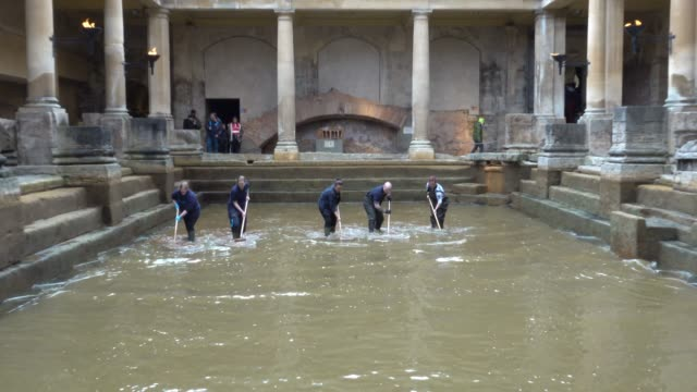 Bath and North East Somerset Council employees brush algae and sludge from the original Roman lead lined floor of the Great Bath as it is drained of...