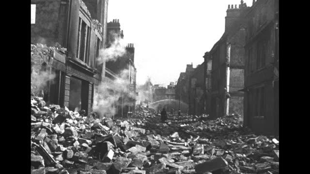 bath in ruins / smoking ruins / man hosing smoking debris / woman walking through brick and debrisfilled street toward watering hoses / brick wall... - 礎石点の映像素材/bロール