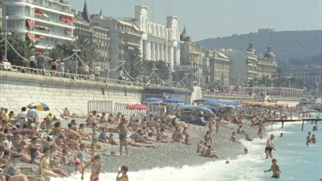 vidéos et rushes de ws bathers along wall on beach and café above sea at nice / nice - 1950