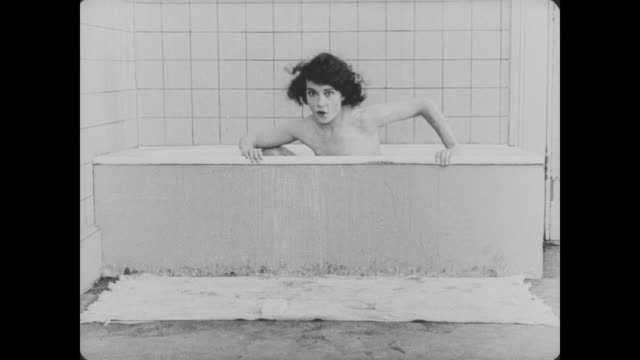 1920 a bathing woman drops a bar of soap outside of the bathtub, and a hand covers the camera so her breasts aren't exposed to the audience when she reaches for the soap - 無声映画点の映像素材/bロール