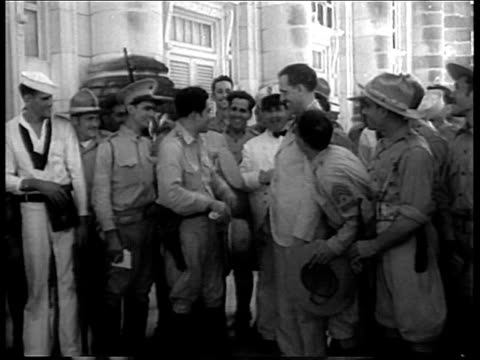 Batista standing wtih other soldiers on street and laughing smiling during revolution / crowd carrying Batista on shoulders on Havana street...