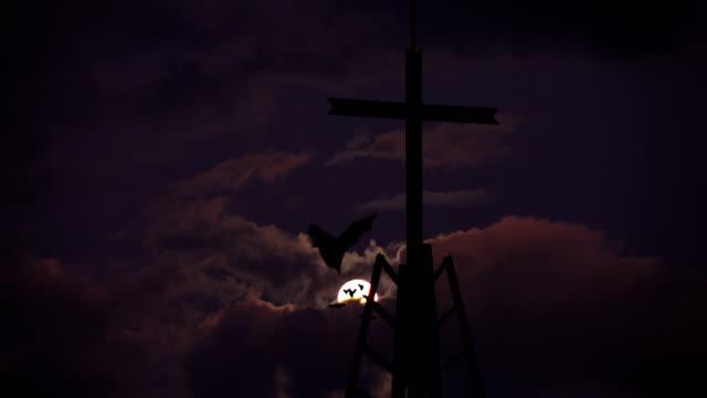 Fledermäuse in der Vollmondnacht und ein Kreuz.