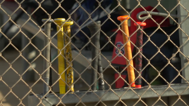 bats in the dugout at a little league baseball game. - slow motion - dugout stock videos & royalty-free footage