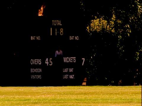 vídeos de stock e filmes b-roll de a batsman runs during a cricket game. - enfeites para a cabeça