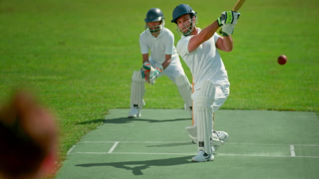 slo mo batsman striking the ball on the sunny playing field - match sport stock videos & royalty-free footage