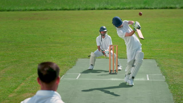 slo mo ld batsman striking the ball thrown by the bowler on the sunny field - cricket video stock e b–roll