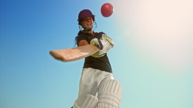 slo mo speed rampa batswoman che colpisce la palla sotto il sole - cricket video stock e b–roll