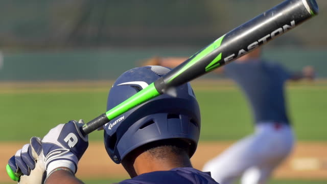 stockvideo's en b-roll-footage met a batter at a baseball game prepares to swing the bat and hit the ball. - slow motion - honkbal teamsport