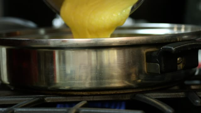 Batter being poured into a skillet for making cornbread.