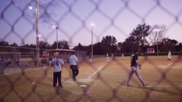 vídeos y material grabado en eventos de stock de batter hits a pop-fly at a men's league softball game. - sófbol