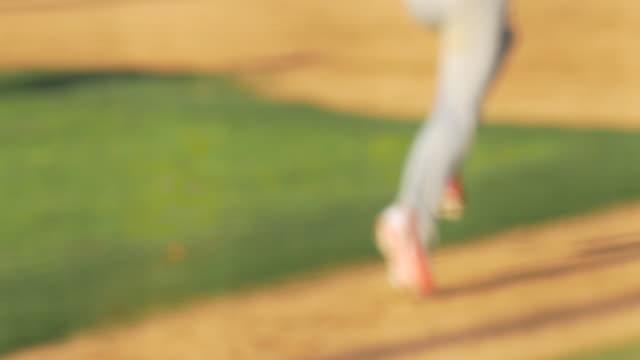 A batter runs to first base at a baseball game. - Slow Motion