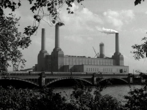 battersea power station and a victorian railway bridge framed by trees. 1958. - 19th century style stock videos & royalty-free footage