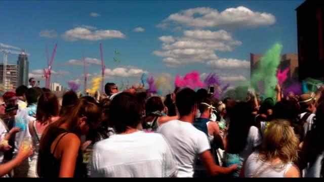 battersea power station hosts hindu holi festival of colours england london battersea power station ext **music heard sot** people throwing paint... - バタシー発電所点の映像素材/bロール