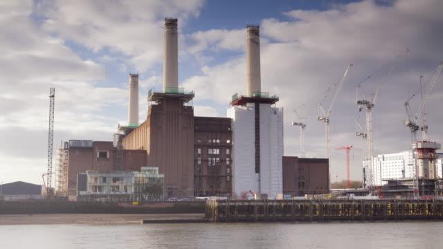 battersea power station on the banks of the river thames, london. - バタシー発電所点の映像素材/bロール