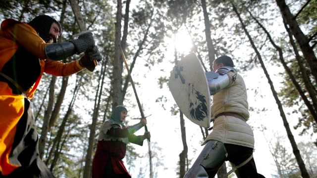 Battle between three aggressive and strong opponents, medieval knights.