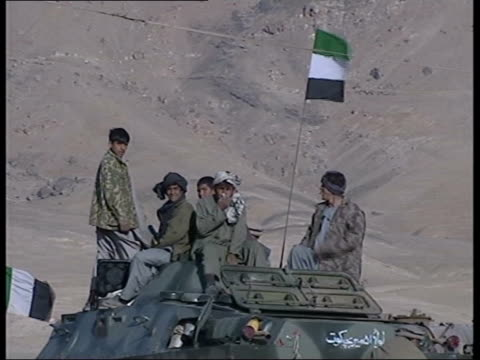 Kabul Two Northern Alliance fighters sitting on tank on guard LMS Alliance soldiers sitting on tank with their flag flying MS Fighters' faces BV...