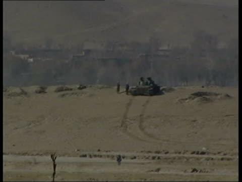 Nr Kabul Maidan Shar Northern Alliance tank taking position on hillside BV Alliance troops positioning large gun SIDE Tank firing BV Large gun fired...
