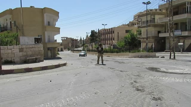 battle of maaloula, syrian civil war. view of a lone armed gunman from harakat ahrar al-sham standing guard on an empty street. - rebellion stock videos & royalty-free footage
