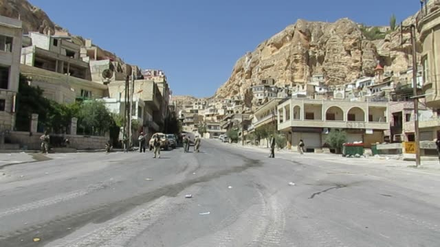 battle of maaloula, syrian civil war. view of armed gunmen from the harakat ahrar al-sham milling on an empty street. - battle stock-videos und b-roll-filmmaterial