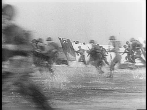 Battle of the Central Pacific / flag flying from ship's masthead / fleet of ships at sea / soldiers run to shore from landing barges / American plane...