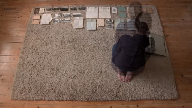 Soldier Barney Griew from Hackney ENGLAND London INT High angle shot SPEEDEDUP / TIME LAPSE footage Sarah Kogan laying out photographs letters and...
