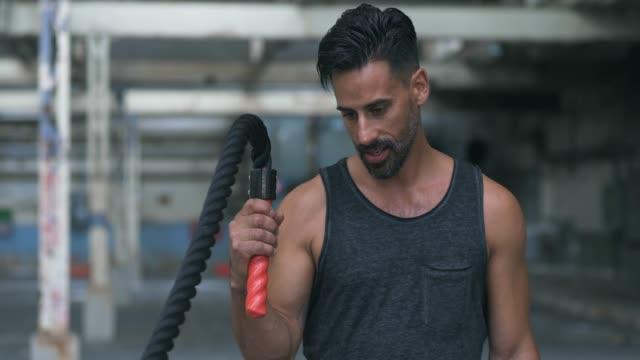 vídeos de stock, filmes e b-roll de exercício de corda de batalha em um armazém abandonado - adulto maduro