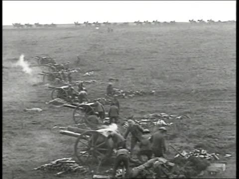 Battlefield w/ line of wheeled artillery firing as soldiers on horseback move along horizon line GRAINY Soldiers on open battle field smoke drifting...
