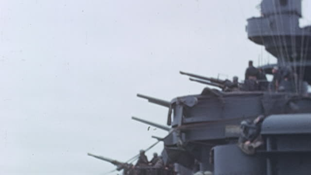 battleship during a naval bombardment with all guns firing at shore / okinawa japan - schlachtschiff stock-videos und b-roll-filmmaterial