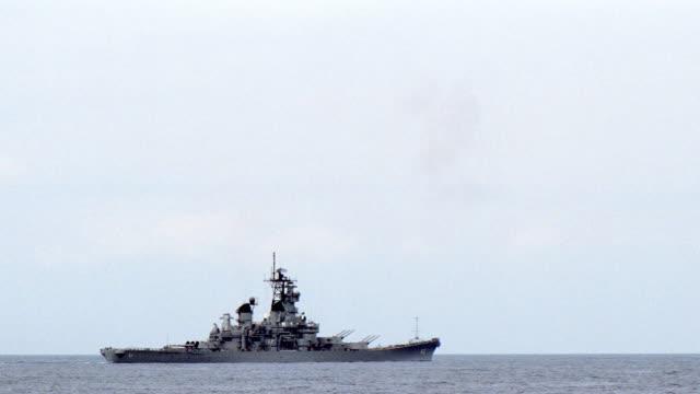a battleship floats on the ocean horizon. - us navy stock videos & royalty-free footage