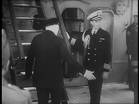 battleship floats through the sea / sailors assembled on deck stand in formation / winston churchill walks onto the deck and salutes the sailors,... - 1941年点の映像素材/bロール