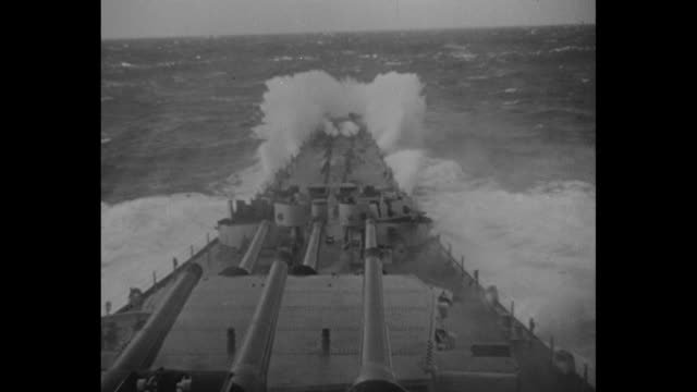 stockvideo's en b-roll-footage met us battleship in the distance cuts though heavy seas as it moves in pacific ocean / a huge wave crashes over ship as seen from above three massive... - geallieerde mogendheden