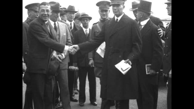 battleship uss idaho moves past camera / us secretary of the navy curtis wilbur shakes hands with john rodgers, commander of the flying boat naval... - heroes stock videos & royalty-free footage