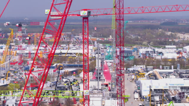 bauma convention munich close flight over exhibition area with cranes in foreground - messen stock-videos und b-roll-filmmaterial