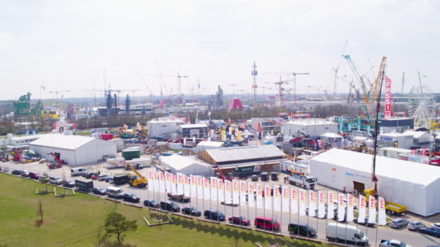 bauma convention munich rise over logos to aerial of exhibition area - messen stock-videos und b-roll-filmmaterial