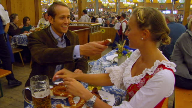 MS Bavarian couple eating pretzels and drinking beer, Oktoberfest, Munich, Germany