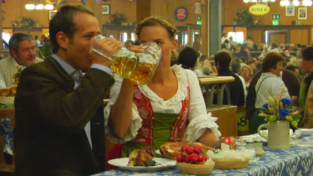 vidéos et rushes de ms bavarian couple in traditional clothes at beer hall, oktoberfest, munich, germany - radis