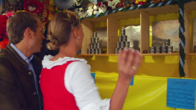 ms bavarian couple in traditional clothes at hit can pyramid booth, oktoberfest, munich, germany - german culture stock videos and b-roll footage